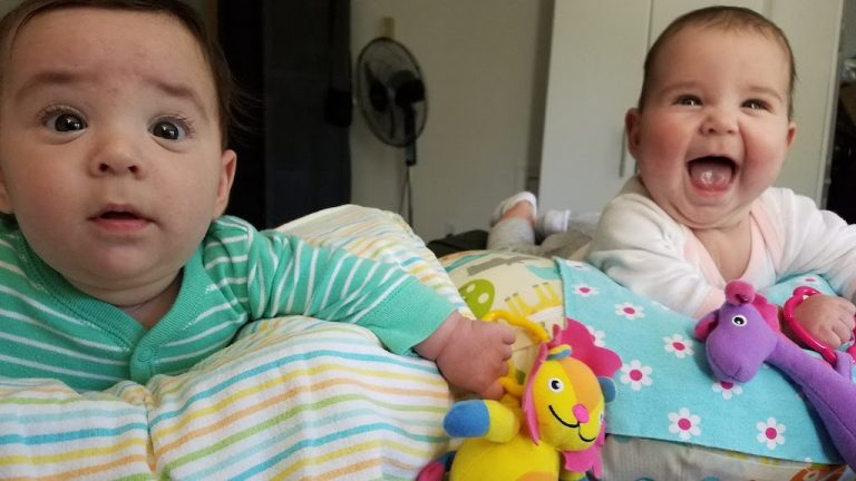 Boy girl twins in gender neutral kids clothes laughing