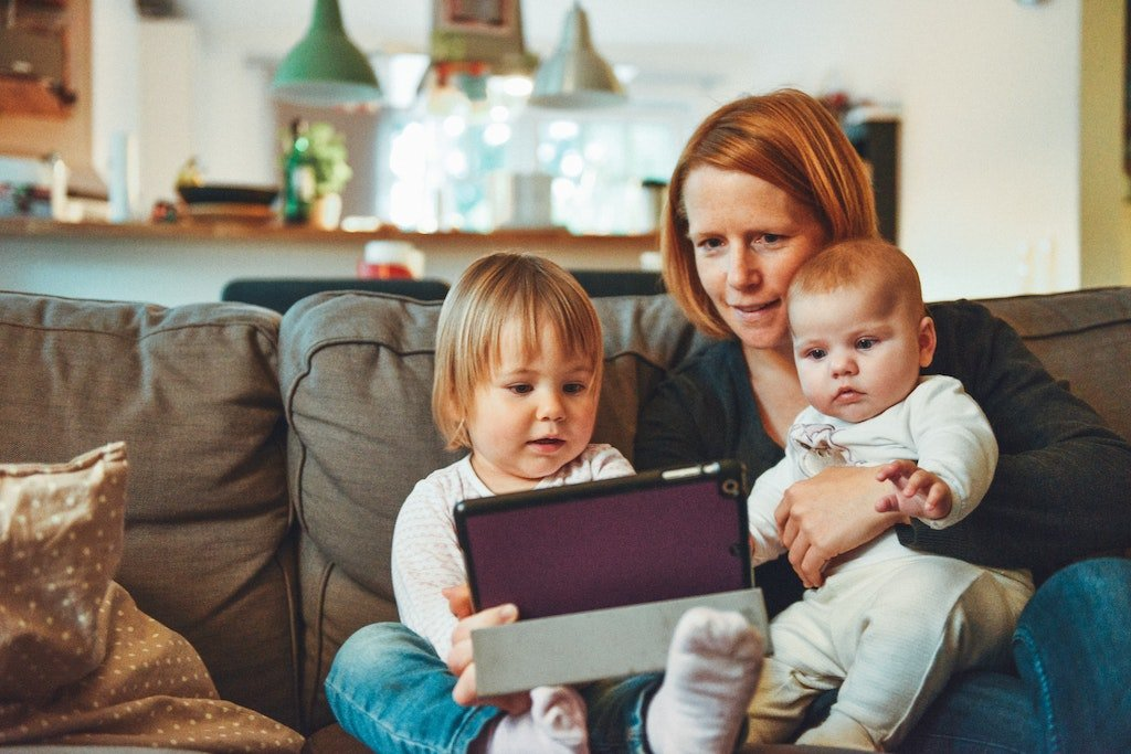 Mom holding kids and a computer