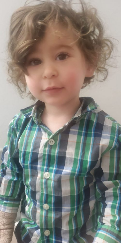 clothes have no gender curly haired child in plaid shirt