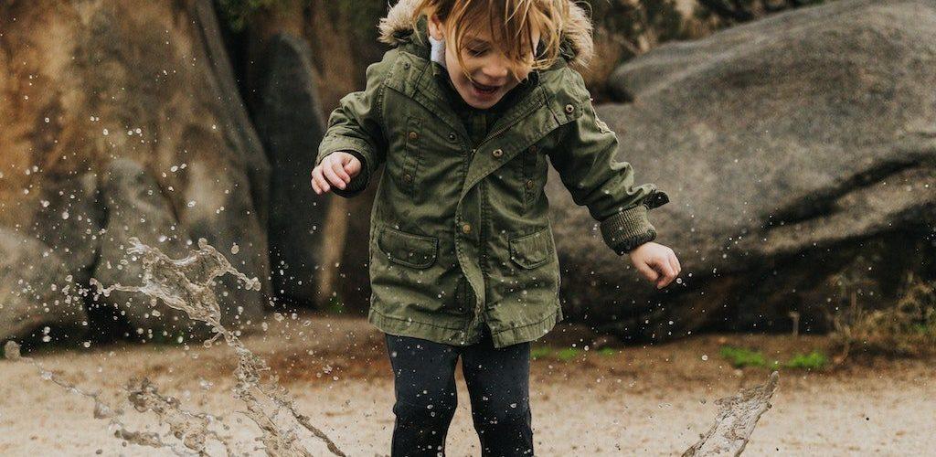 kid splashing in water in gender neutral kids clothes